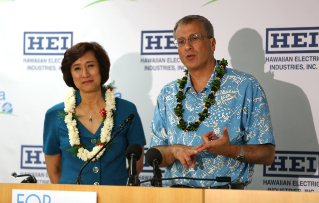 Jim Robo Chairman and CEO, NEXTERA Energy, Inc. gestures with Connie Lau, President and CEO Hawaiian Electric Industries while speaking at press conference announcing a merger with NEXTERA at suite 800, 1001 Bishop Street. Honolulu, Hawaii.  3 dec 2014. photograph by Cory Lum
