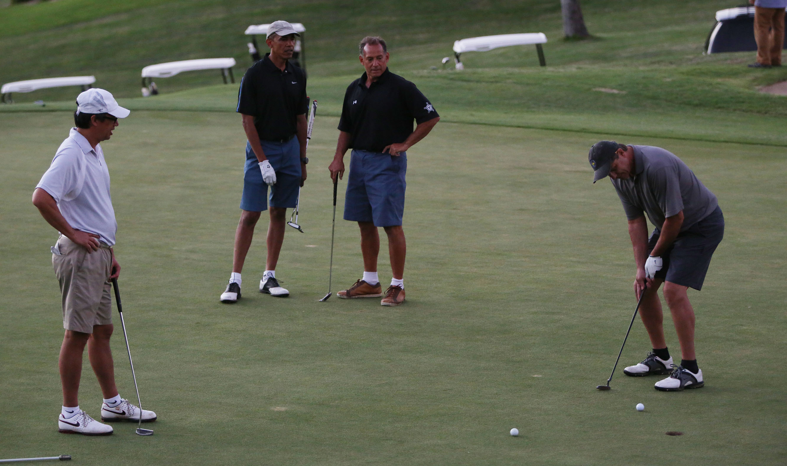 President Barack Obama stands with his childhood friend, Bobby Titcomb, as Greg Orme makes a putt and Mike Ramos watches Tuesday on the 18th green at Mid Pacific Country Club.