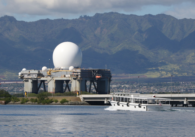 SBX missile defense domed platform rests in Pearl Harbor as a USS Arizona Memorial ferry heads thru Pearl Harbor near the Ford Island bridge. 7 dec 2014. photograph Cory Lum