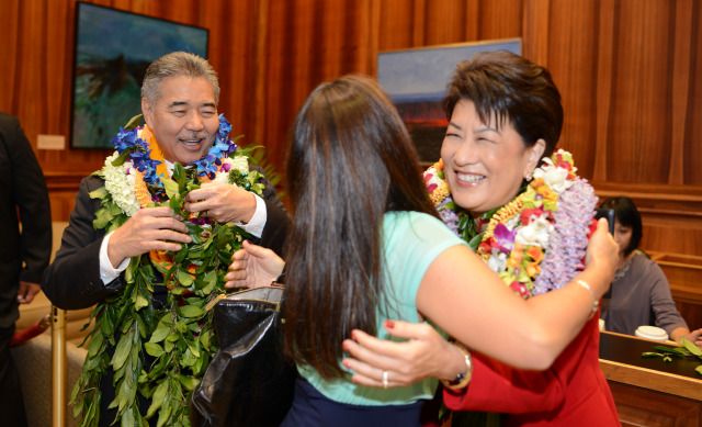 Governor David Ige adjusts his lei as a supporter places a lei on the First Lady Dawn Ige in their first photo opportunity on the 5th floor lobby area of the Governor's office at the Capitol Building. 1 dec. 2014. photo Cory Lum