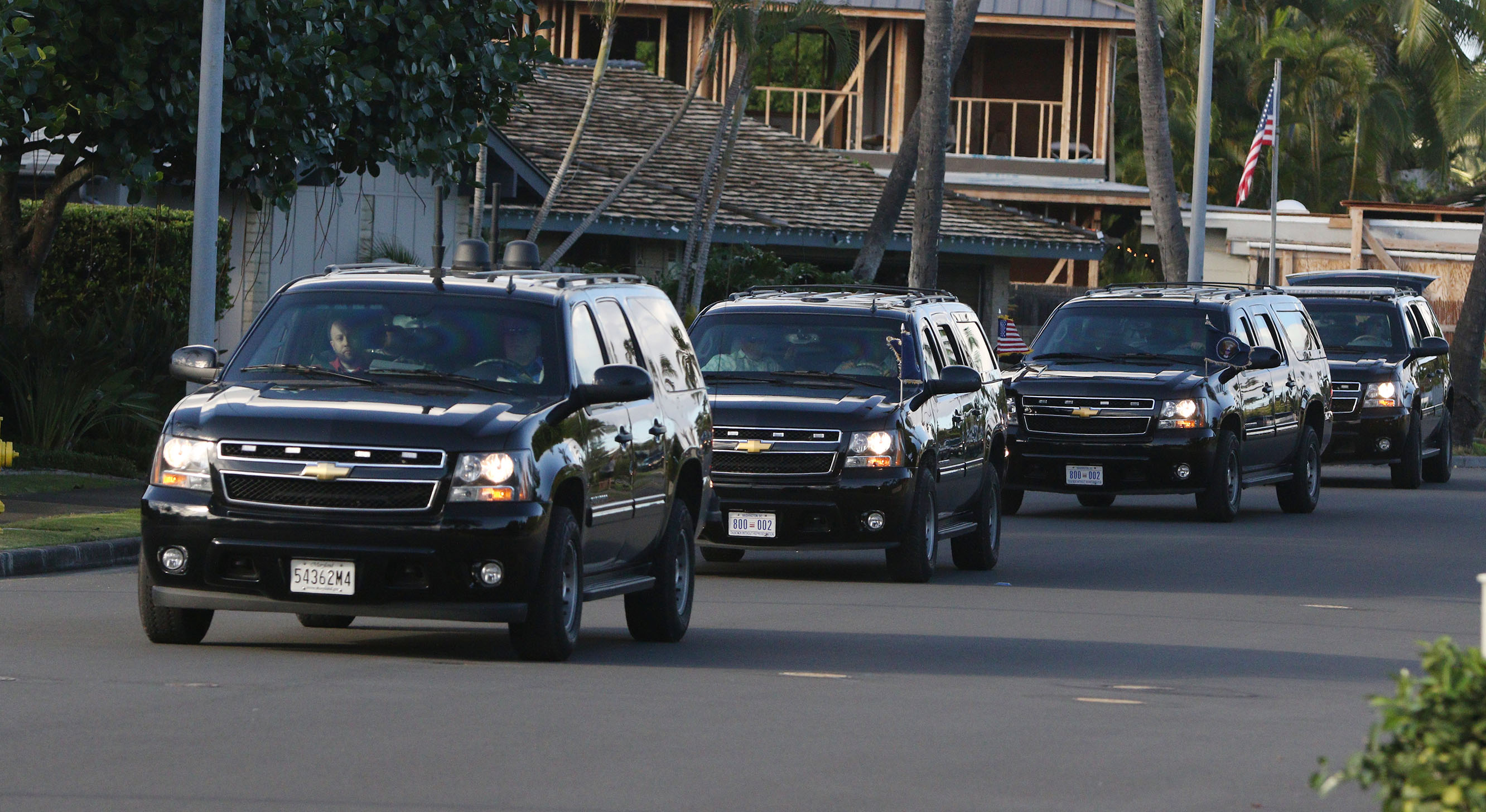 President Barack Obama's motorcade rolls out of his Kailua vacation neighborhood on its way to the Marine Corps Base in Kaneohe. Unlike during vacation stops such as the First Family made earlier in the day at the Bellows Air Force Station beach, this time his car sported American and presidential flags.