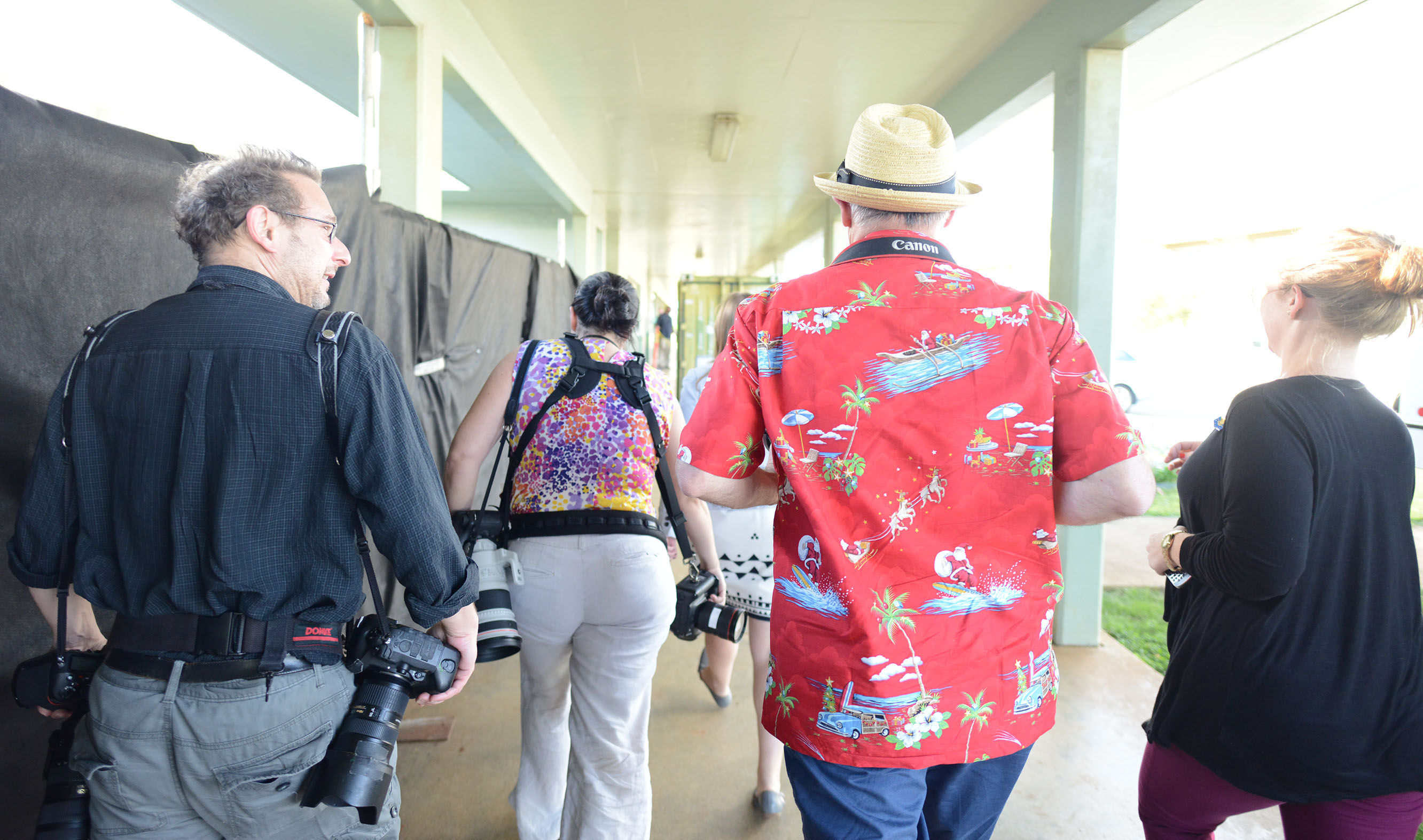 White House travel pool photographers hustle to get to their positions outside Anderson Hall at Marine Corps Base Hawaii for a presidential address to an audience of 75-100 service members and their relatives.