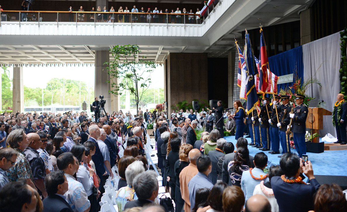 Audience members stand as singer Raiatea Helms performs the national anthem.