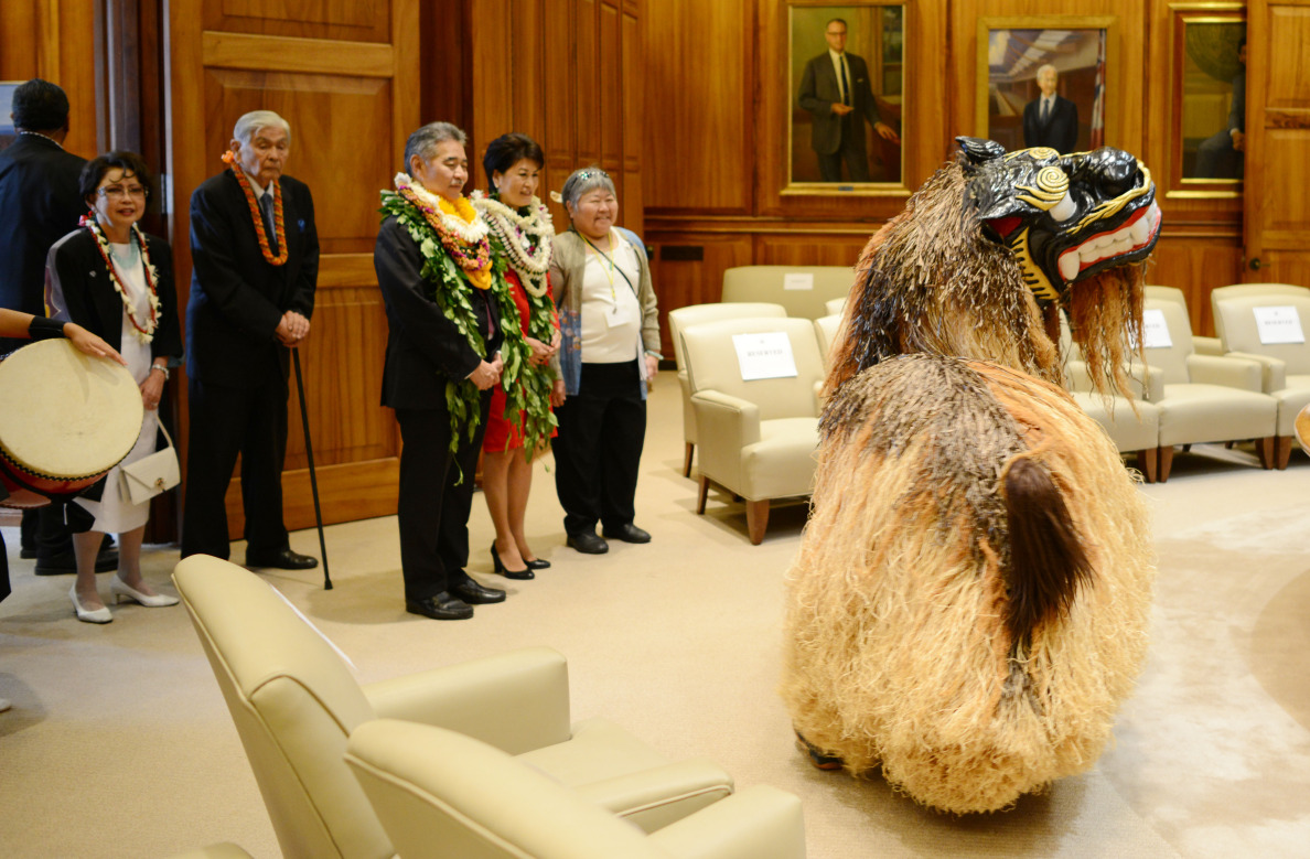Gov. David Ige and First Lady Dawn Ige watch as a Shishimai Lion lion dog makes an appearance in the governor's office just before a public open house.