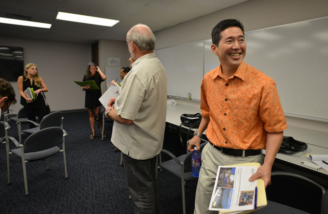 Left, Hawaiian Electric Vice President Colton Ching packs up on his way to his next appointment after press conference. 20 jan 2015. photograph Cory Lum/Civil Beat