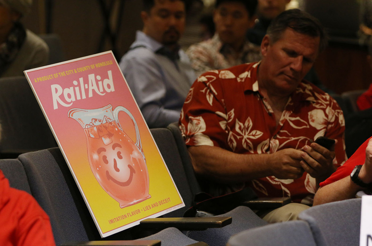 A protest sign derides 'Rail-Aid' as an 'Imitation Flavor' and 'A Product of the City & County of Honolulu.'