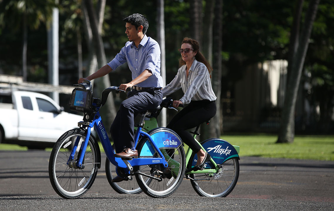 Ben Trevino and Lori McCarney and ride their Bikeshare Hawaii bicycles near Iolani Palace.  7 jan 2015.photograph Cory Lum/Civil Beat