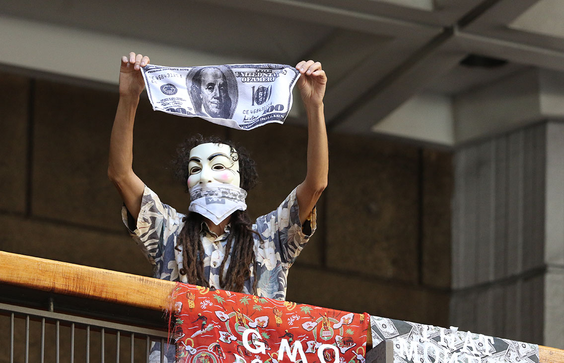 A masked demonstrator waves an oversized $100 bill on the first floor of the Capitol near anti-GMO signs.