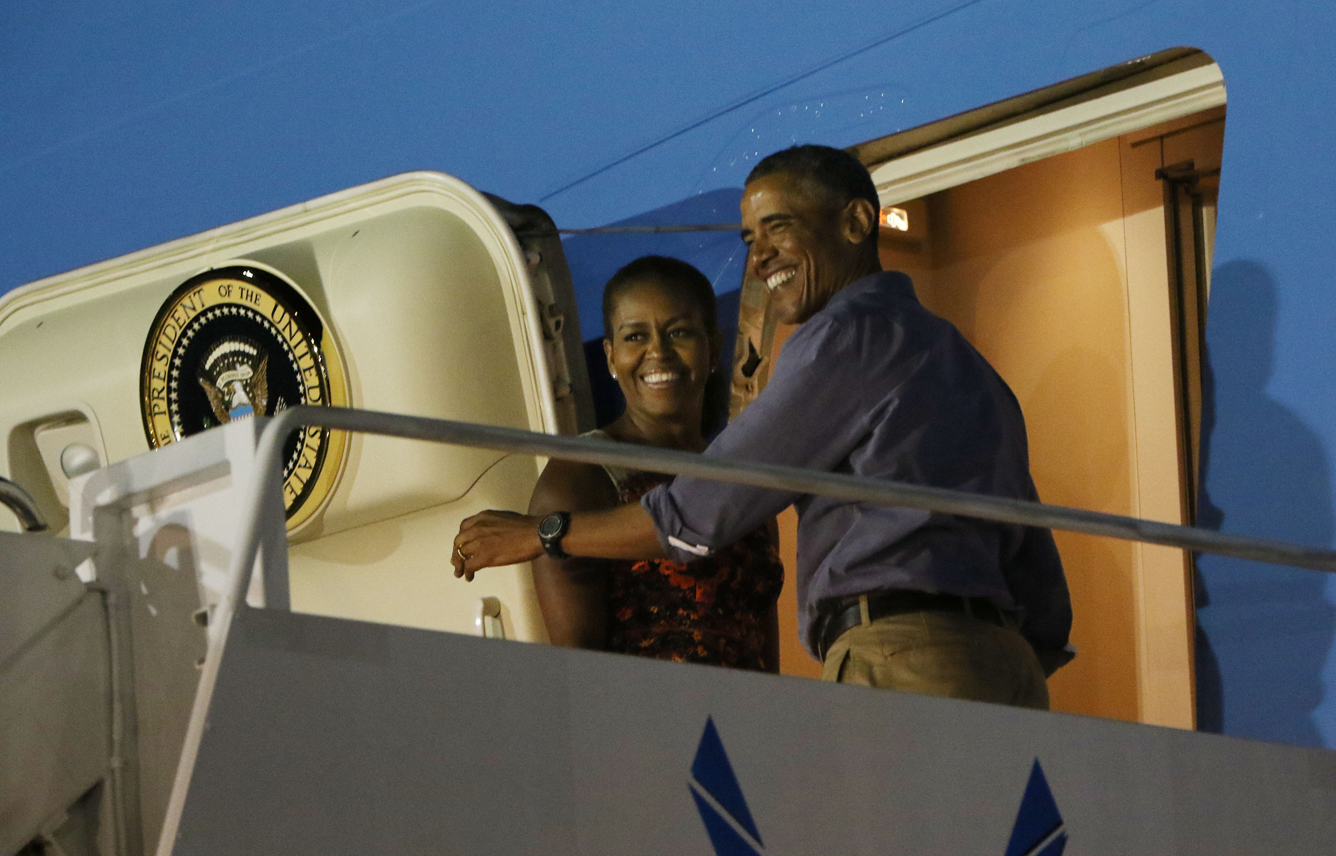 President Obama and First Lady Michelle Obama smile at well-wishers as they board Air Force One and end their 16-day holiday vacation on Oahu.