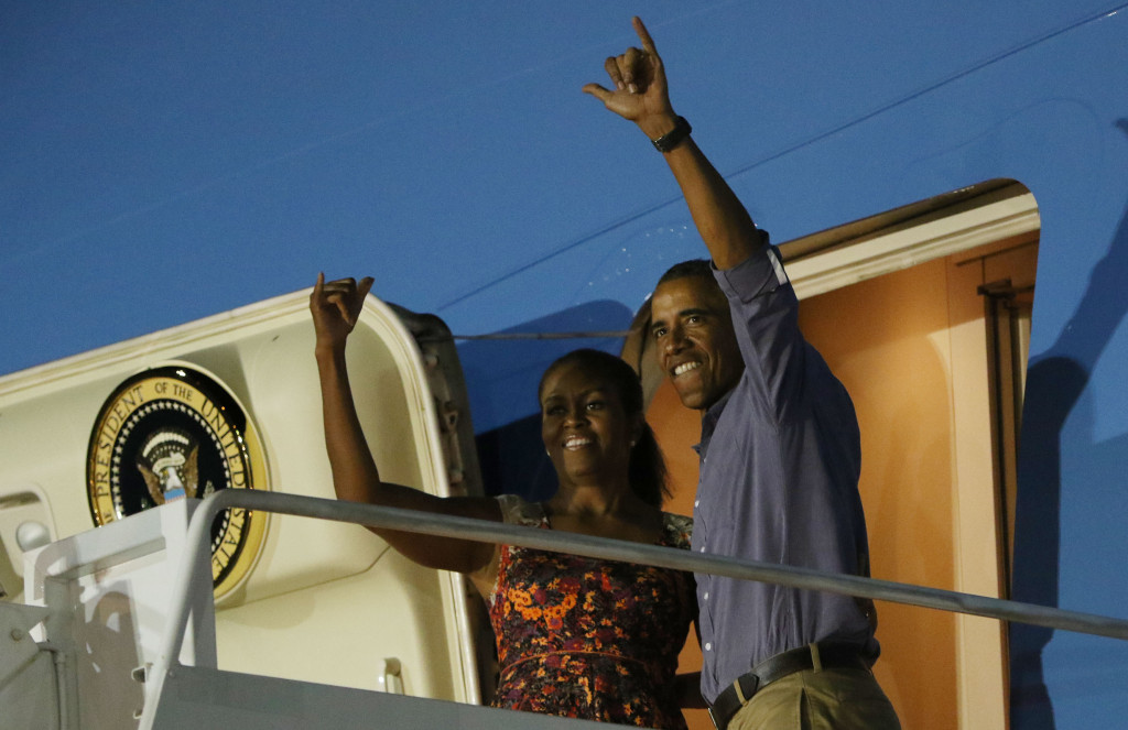 President Barack Obama and First Lady Michelle Obama give a shaka as they board Air Force One at Joint Base Pearl Harbor Hickam. 3 jan 2015. photograph Cory Lum/Civil Beat