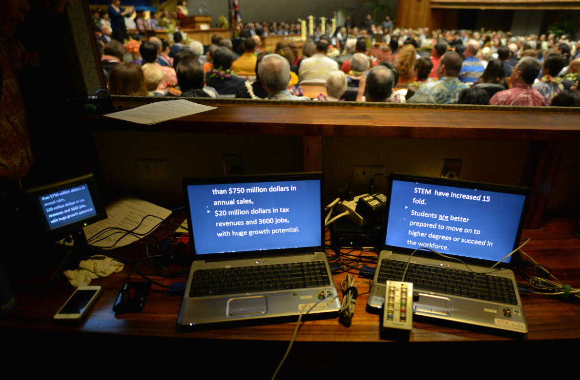 Laptops scroll Senate President Donna Mercado Kim's speech on teleprompters as she addresses the floor and the gallery.