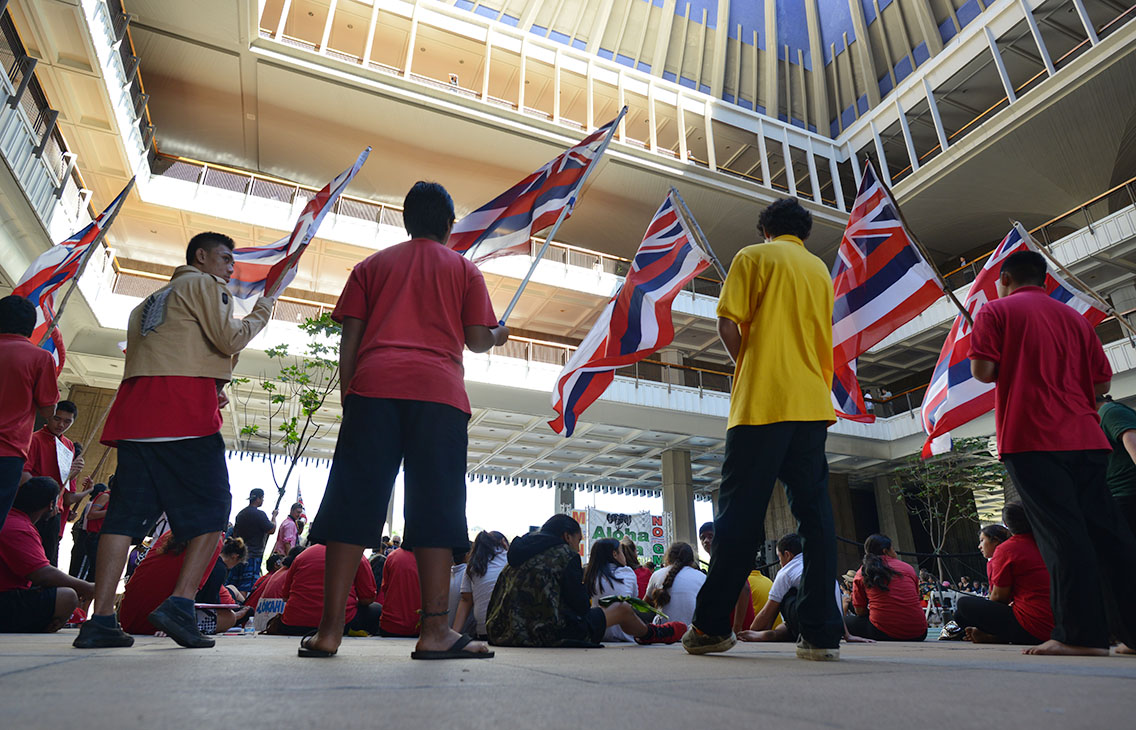 Students, some of them waving Hawaii state flags, occupy the Capitol rotunda on Wednesday morning.