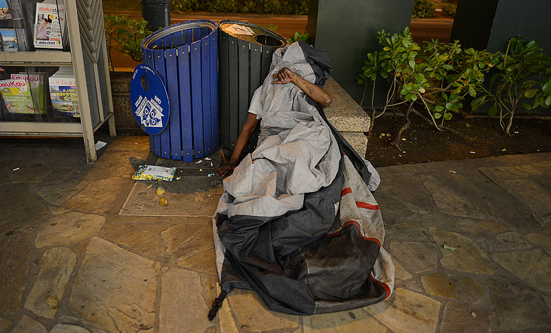 Tarp covered man as he rests along Kalakaua Avenue.  9 jan 2015. photograph Cory Lum/Civil Beat