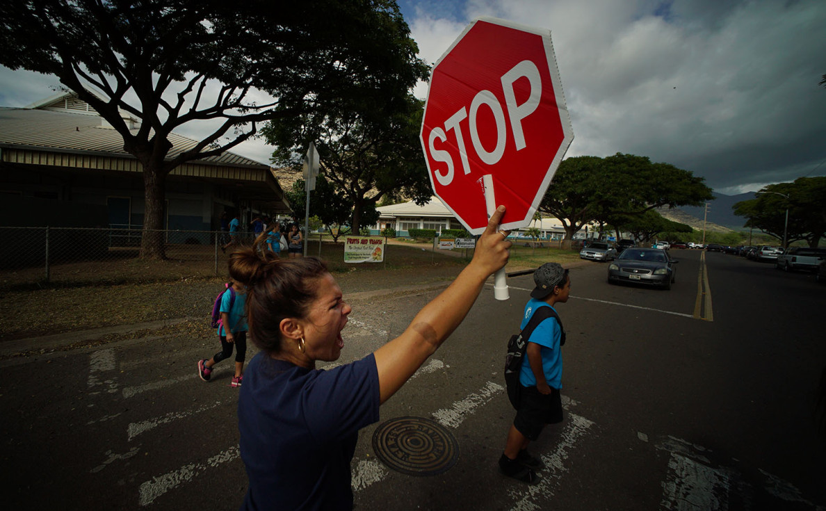 Crossing guard Brandie Magno assists students leaving Kamaile Academy on Monday.
