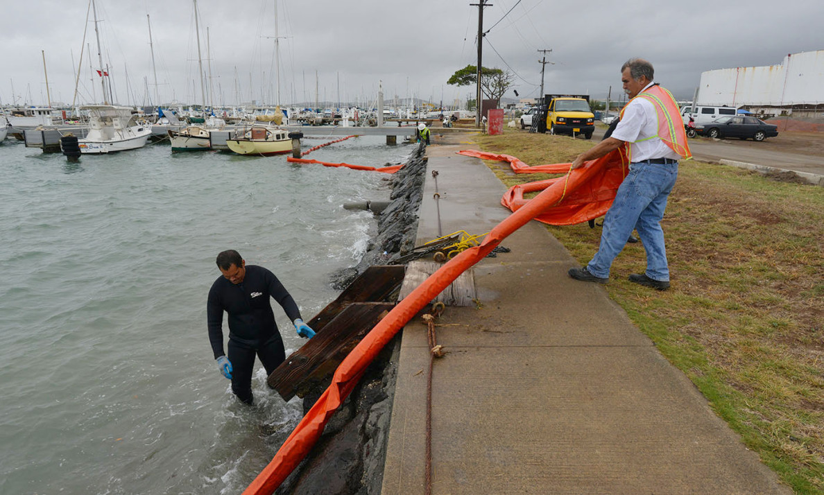 Workers adjust the floating barrier at Keehi Lagoon on Tuesday. The leading edge of the plume of spilled fuel had reached within 150 feet of the water.