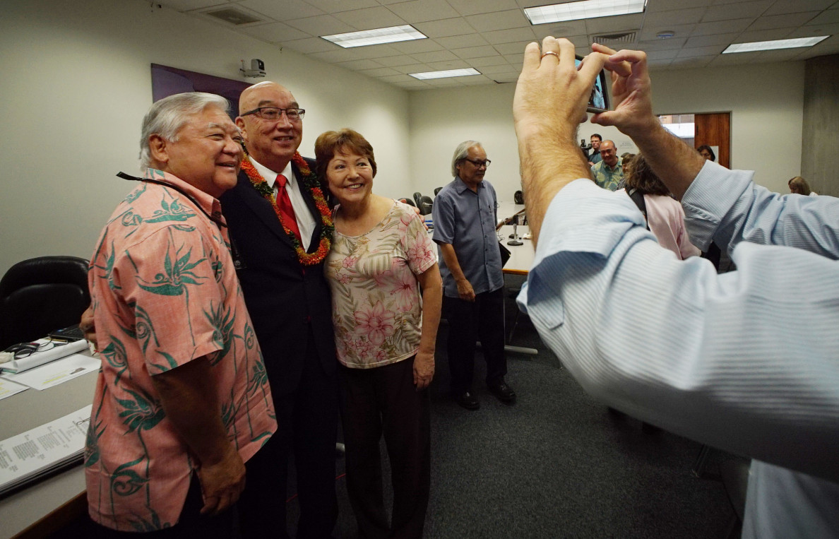 Sen. Clarence Nishihara, left, Randy Iwase and Sen. Michelle Kidani pose for photos after Iwase's confirmation hearing.