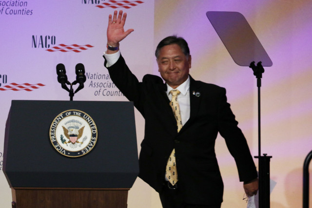 Maui City Council member and National Association of Counties President Riki Hokama waves to crowd before giving a short speech and before introducing Vice President Biden at the Washington Marriot Wardman Park.  23 feb 2015. photograph Cory Lum/Civil Beat