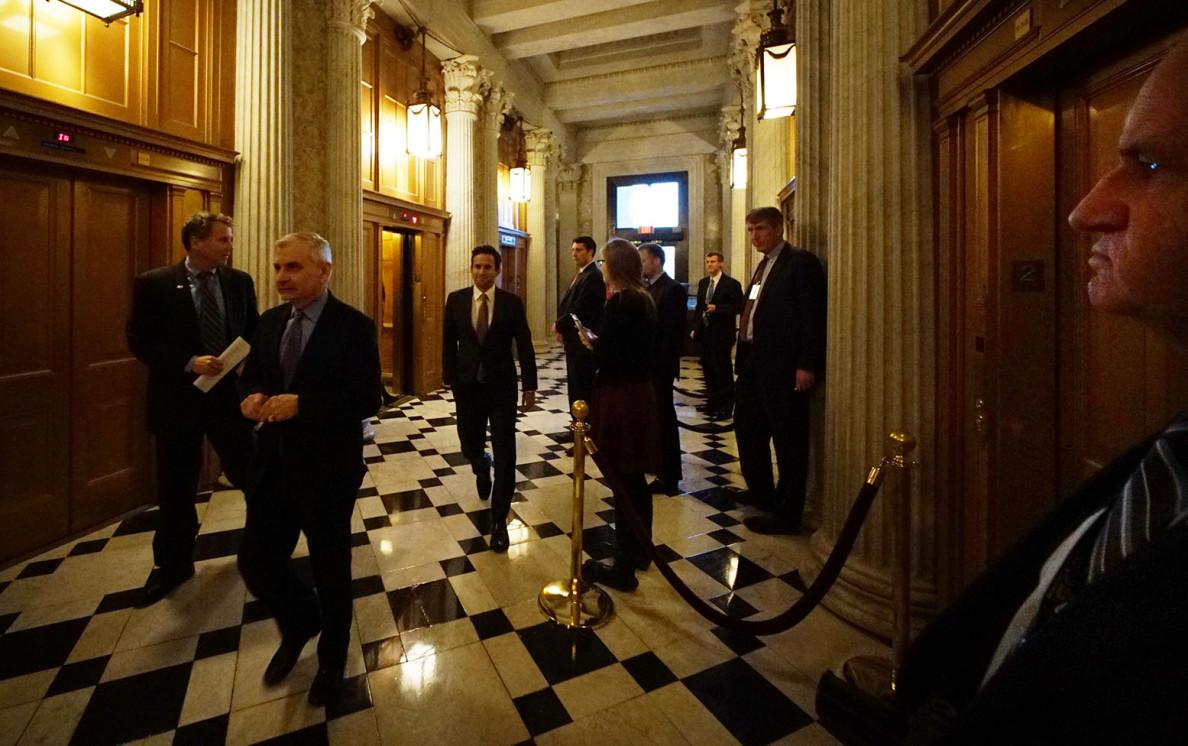 U.S. Sen. Brian Schatz of Hawaii, center, walks toward the Senate Chamber entrance Monday.