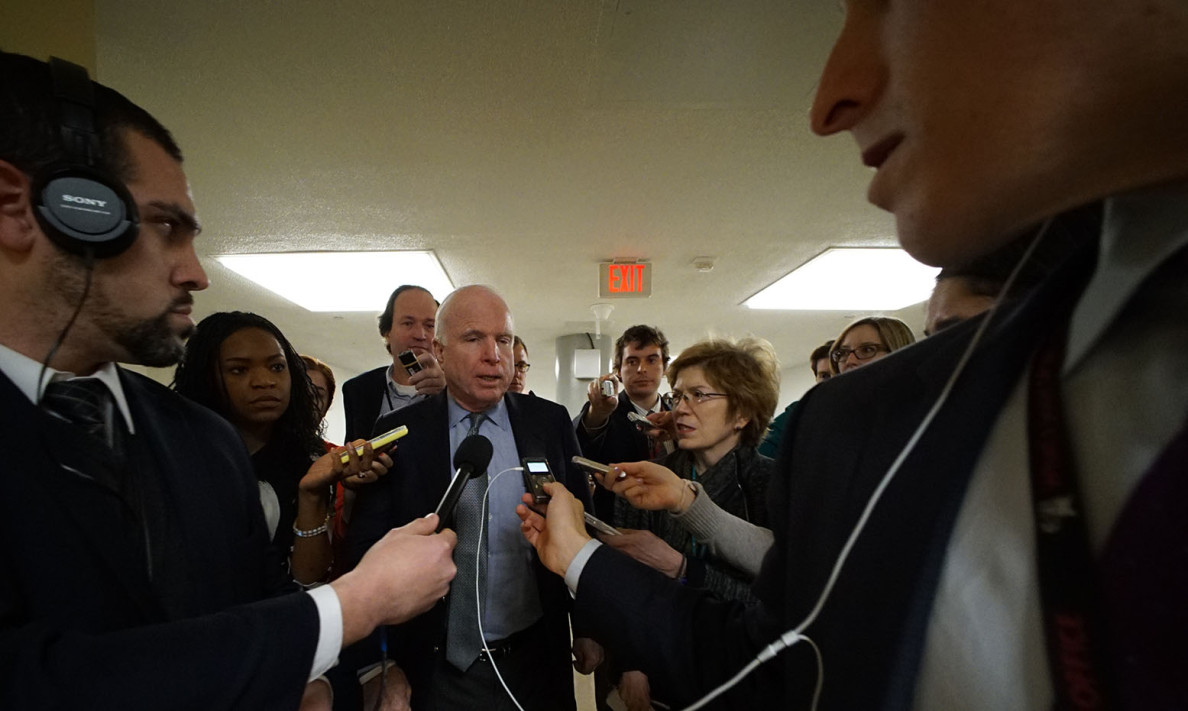 Arizona Sen. John McCain gets the attention of reporters in the Capitol basement Monday on his way up to cast a vote in the Senate Chamber.