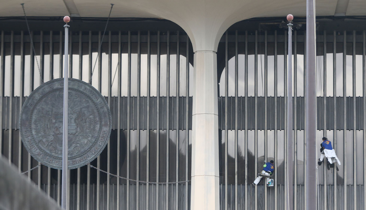 Window washers remove bird waste from the splattered windows of the Hawaii State Capitol on Thursday as legislators conducted their business inside.