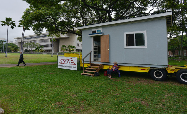 Faith Action for Community Equity (F.A.C.E.) displays a house with two rooms with two bunk beds made using a shipping container parked on the mauka side of Honolulu Hale. 3 feb 2015. photograph Cory Lum