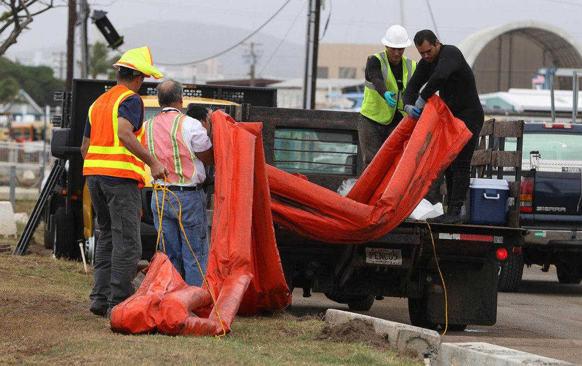 Workers load portions of the floating barrier, which are monitored daily, into a truck at Keehi Lagoon.