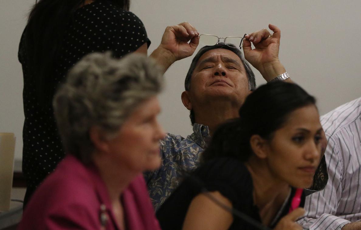 State Rep. Bertrand Kobayashi checks his glasses Saturday during testimony regarding medical marijuana dispensaries.