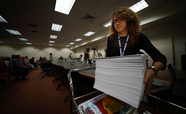 Legislative Analyst from Representative Kaniela Ing's office carry's a large pile of written testimony at room #325 today.  11 feb 2015. photograph Cory Lum/Civil Beat