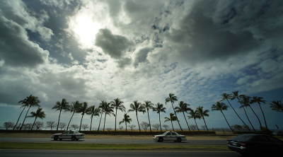 HPD police vehicles rip along Farrington Highway with clouds and sunset. 13 feb 2015. photograph Cory Lum/Civil Beat
