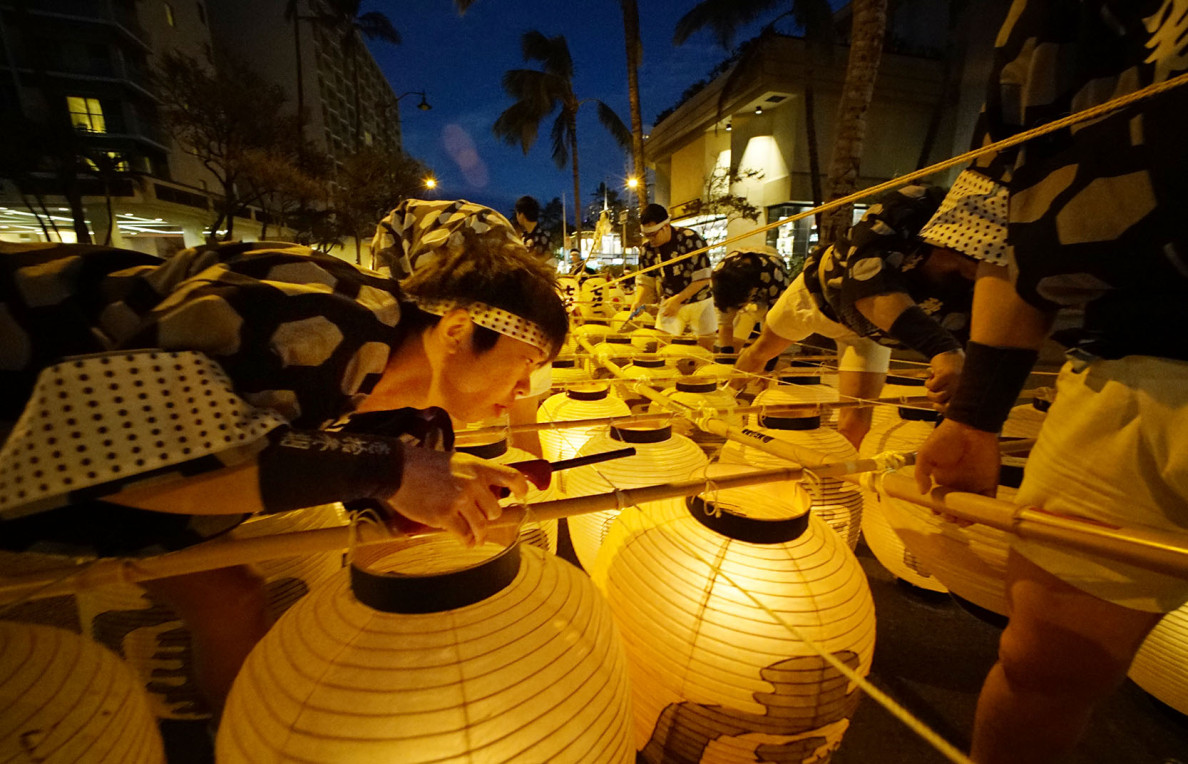 Performers from Akita Kanto light their candles in preparation for their performance in front of the Moana Surfrider Hotel on Sunday night during the Honolulu Festival. Kanto lanterns are suspended by bamboo and weigh almost 100 pounds balanced by performers.