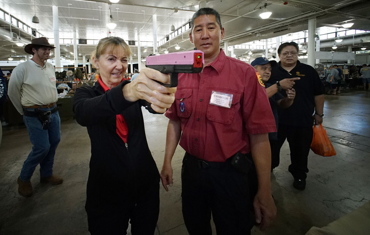 Jan Gardner tries out a training pistol under the watchful eye of firearms instructor Clifford Goo at the gun show.