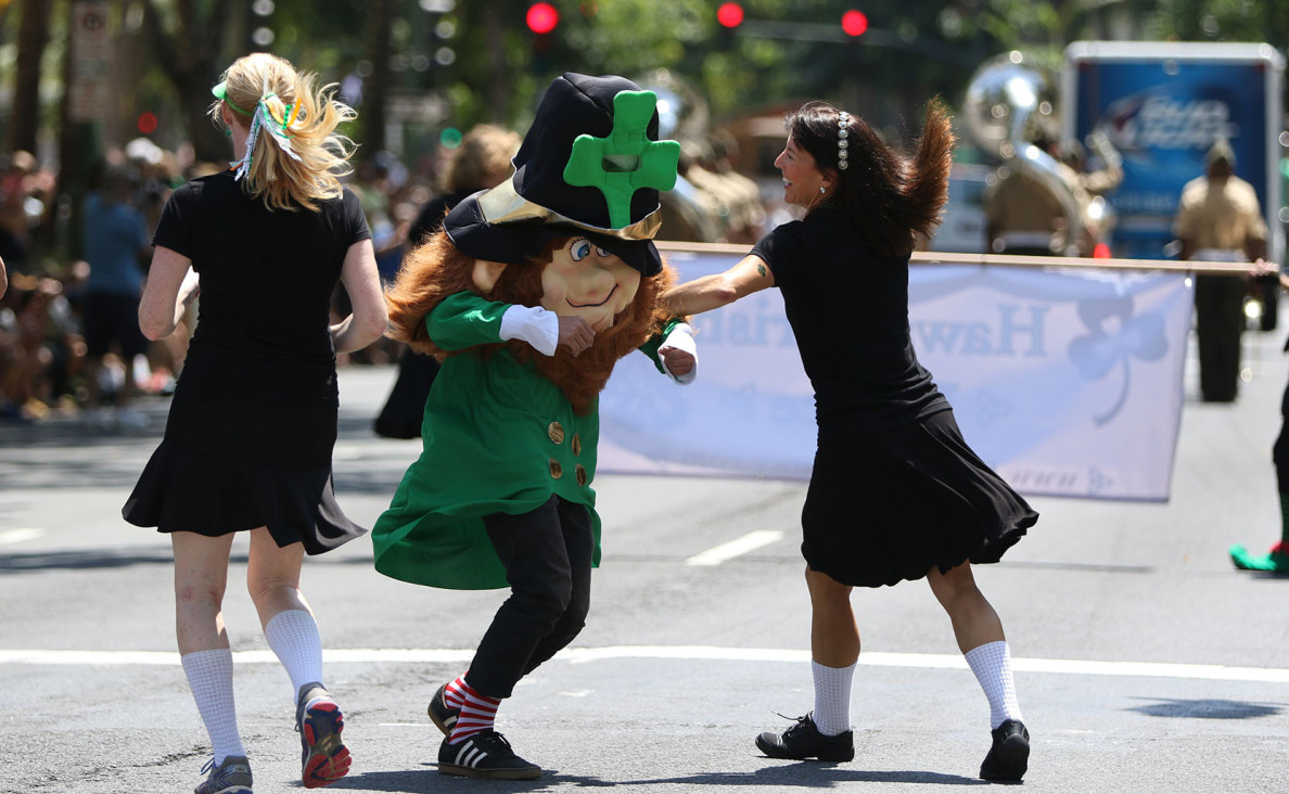 Tiger Jones as a leprechaun named 'Shamous' dances with other parade participants as the procession makes its way from Fort DeRussy to Kapiolani Park.