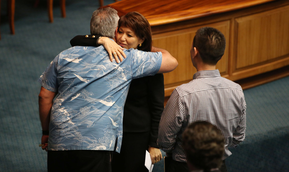 Senate President Donna Mercado Kim hugs the gubernatorial chief of staff, Mike McCartney, after he handed her a letter from Gov. David Ige on Wednesday announcing his withdrawal of the controversial nomination of Carleton Ching to head the Department of Land and Natural Resources.