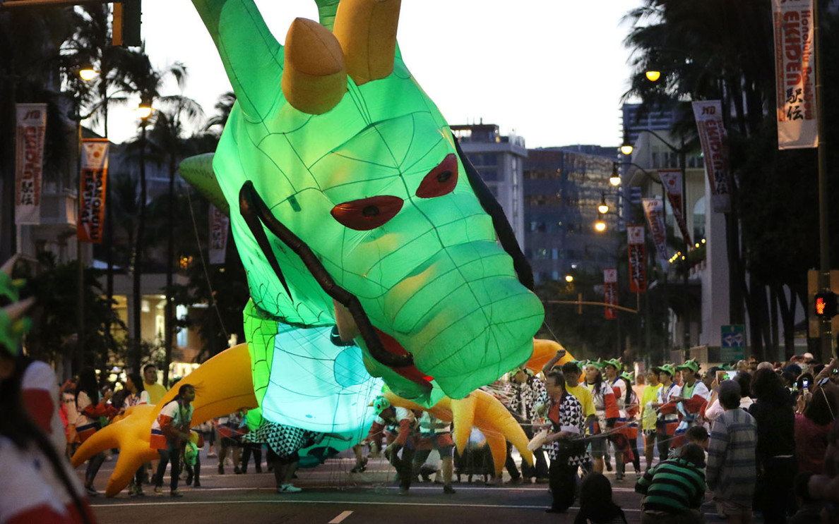 A 'Rising Dragon' dwarfs handlers along Kalakaua Avenue during a climactic parade. The festival promotes ethnic harmony between the people of Hawaii and the Pacific Rim.