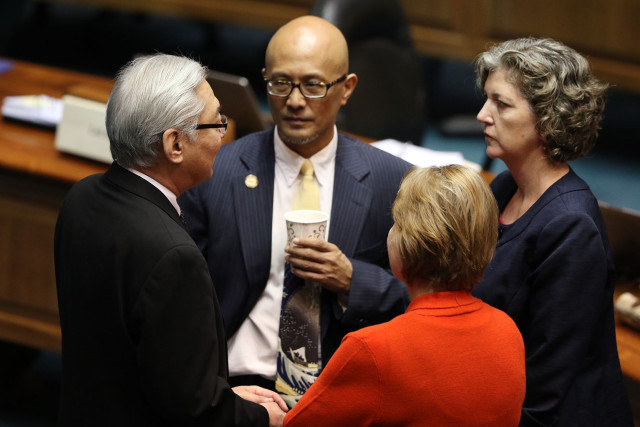 Right, Senator Laura Thielen speaks to left, Senator Les Ihara with Senator Will Espero, center and with back facing camera, Senator Ros Baker during recess before Governor withdrew his nomination.  18 march 2015. photograph Cory Lum/Civil Beat
