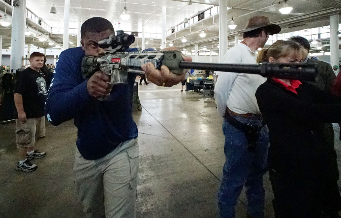 Firearms instructor Cofi Jackson demonstrates an AR15 with a Shot Indicating Resetting Trigger at the gun show this past weekend, at the Blaisdell Exhibition Hall.