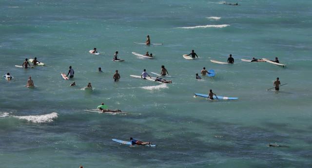 Surfers enjoy the beach off shore Waikiki Beach. 24 dec 2014. photograph Cory Lum