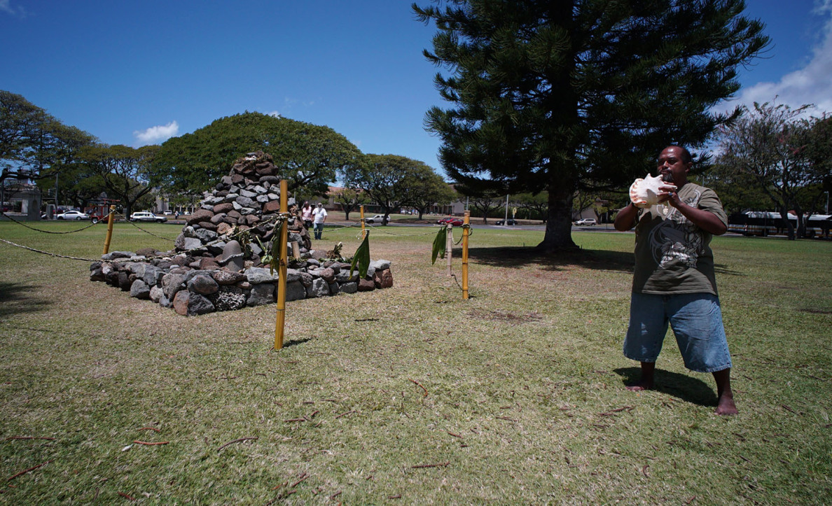 Joseph Madela from Kualoa blows a conch next to an ahu during the demonstration Monday near UH Manoa's Bachman Hall.