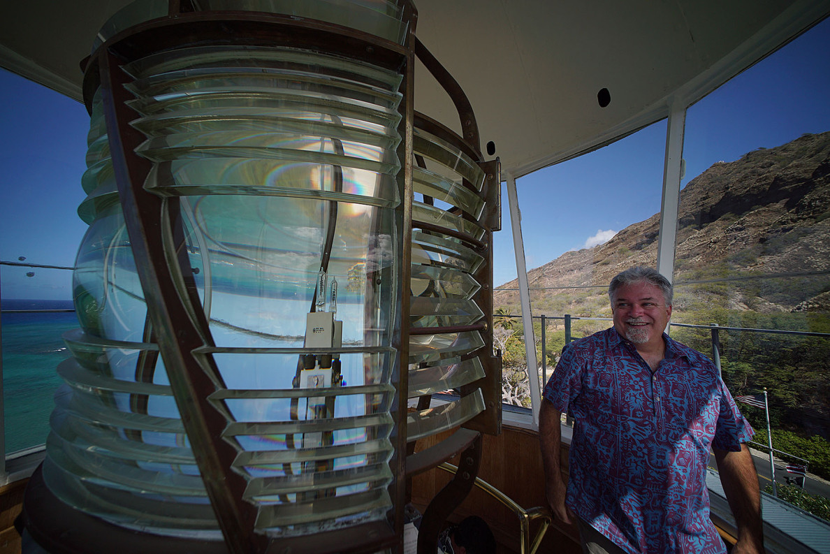 Gary Thomas, US Coast Guard Commander retired seen with a view of the giant fresnel of the Diamond Head lighthouse.  17 april 2015. photograph Cory Lum/Civil Beat