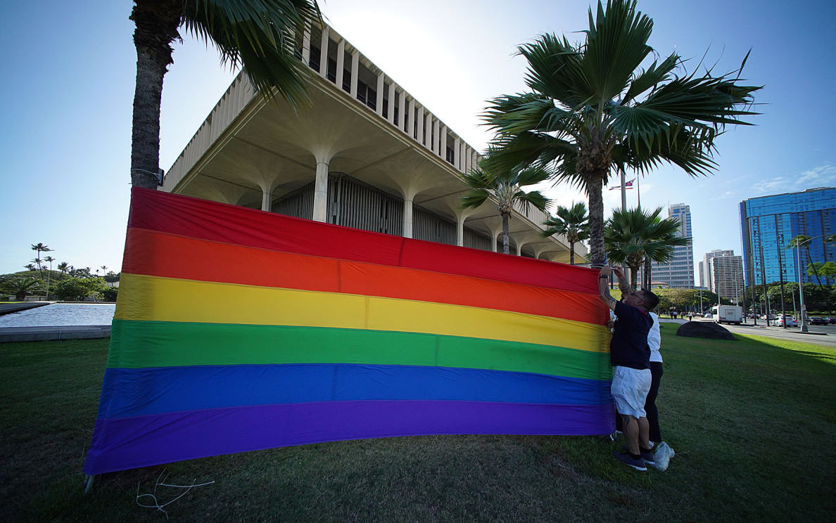 Gay rights supporters raise a rainbow banner Tuesday at the Capitol on the eve of the U.S. Supreme Court hearing arguments about whether to allow same-sex marriages nationwide.