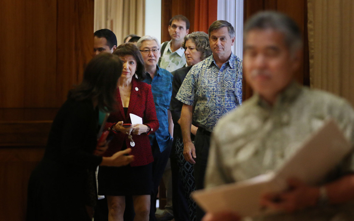 Gov. David Ige leads an entourage into his office Thursday to announce a modified agreement to preserve 665 acres from development at Turtle Bay Resort on the North Shore.