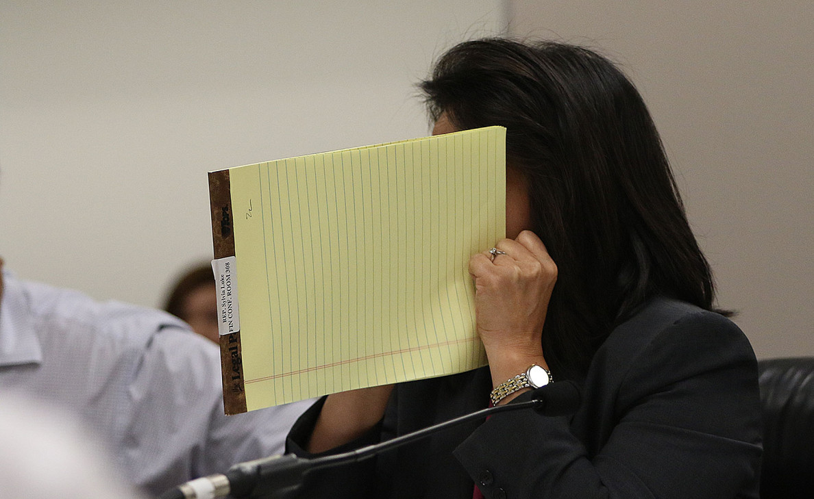 House Finance Chair Sylvia Luke jokingly holds a notepad so people can't read her lips before a conference committee hearing Thursday on the proposed extension of a tax surcharge to pay for the Honolulu rail project.
