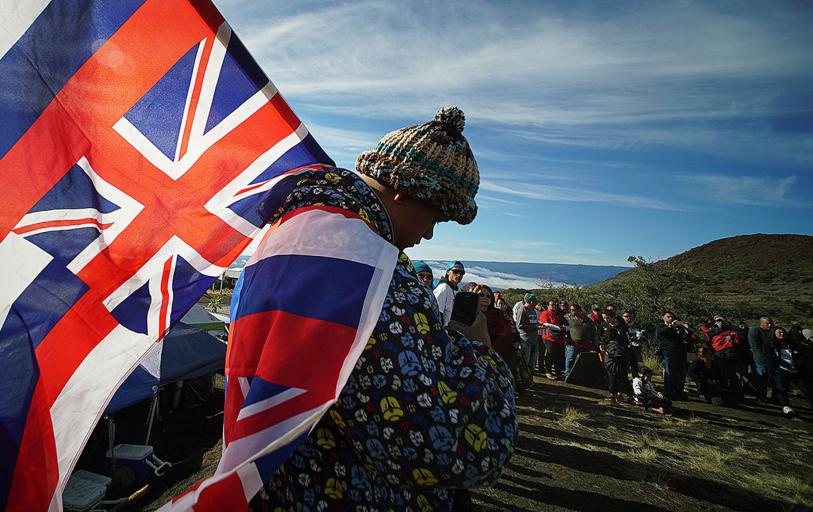 Big Island resident Kalae Kauwe is draped in Hawaiian flags during hula dancing near the Mauna Kea visitors center.