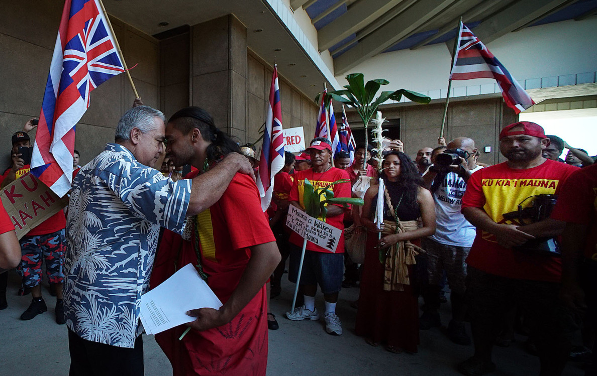 Governor Ige's Chief of Staff Mike McCartney greets Laniakea XX with honi outside the Governor's office. 21 april 2015. photograph Cory Lum/Civil Beat