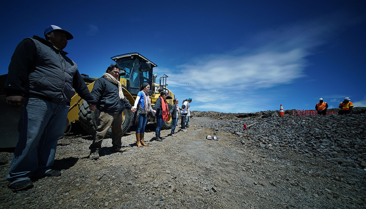 Demonstrators gather last Saturday near the Mauna Kea summit where a blockade of the TMT construction site has been established. Security guards, right, keep watch.
