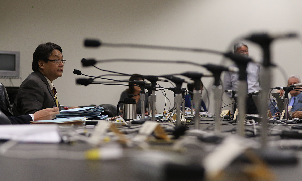 Rep. Mark Nakashima and a bank of microphones during a meeting at the Capitol this week.