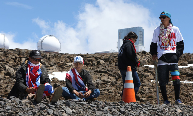 Demonstrators sit and rest on the TMT site after praying and singing.  10 april 2015. photograph by Cory Lum/Civil Beat