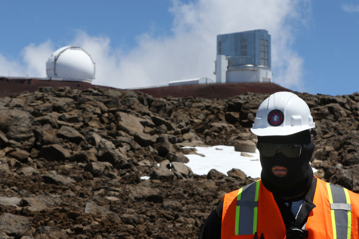 A masked guard watches demonstrators sing and pray near the TMT construction site.  Officials say the telescope would pull in views at the edge of the observable universe.