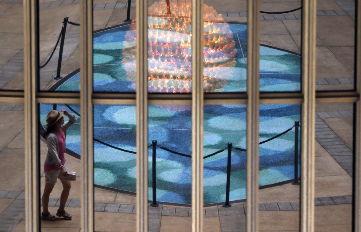 A visitor is reflected in the Senate windows Wednesday at the Hawaii State Capitol.