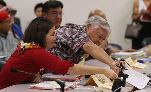 WAM Chair Jill Tokuda and Senator Clarence NIshihara both reach out for bill that Rep Sylvia Luke tossed across the table. 1 may 2015. photograph by Cory Lum/Civil Beat